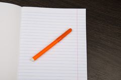 School notebook paper. orange markers. Notebook in line and pencil. open notebook on a brown background. planning. stationery stock images
