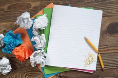 School notebooks and crumpled paper balls. School notebooks, broken pencil and colored crumpled paper balls on old wooden background, top view. Conceptual photo royalty free stock photography