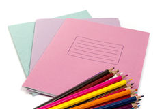 School and office stationery. A stack of colored pencils lying on top of a stack of three copybooks on white background Royalty Free Stock Photo