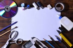 A school or office still life with a white blank sheet of paper and many office supplies. The school supplies lie on a brown wood. En background. Place for text Royalty Free Stock Photos