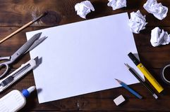 A school or office still life with a white blank sheet of paper and many office supplies. The school supplies lie on a brown wood. En background. Place for text Royalty Free Stock Photography