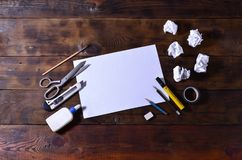 A school or office still life with a white blank sheet of paper and many office supplies. The school supplies lie on a brown wood. En background. Place for text Royalty Free Stock Image