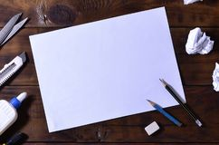 A school or office still life with a white blank sheet of paper and many office supplies. The school supplies lie on a brown wood. En background. Place for text Stock Image