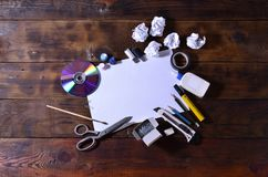 A school or office still life with a white blank sheet of paper and many office supplies. The school supplies lie on a brown wood. En background. Place for text Stock Photo