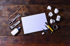 A school or office still life with a white blank sheet of paper and many office supplies. The school supplies lie on a brown wood. En background. Place for text Stock Photography