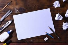 A school or office still life with a white blank sheet of paper and many office supplies. The school supplies lie on a brown wood. En background. Place for text Royalty Free Stock Photo