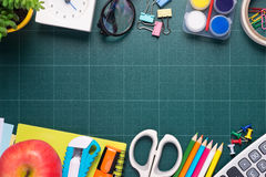School and office supplies and apple in front of blackboard. Stock Images