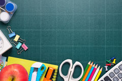 School and office supplies and apple in front of blackboard. Royalty Free Stock Image
