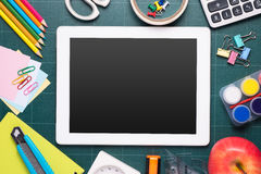 School and office supplies and apple in front of blackboard. Stock Photography