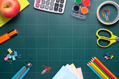 School and office supplies and apple in front of blackboard. Royalty Free Stock Photos