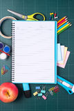 School and office supplies and apple in front of blackboard. Stock Photos