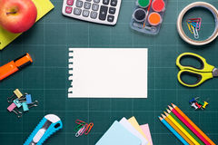 School and office supplies and apple in front of blackboard. Royalty Free Stock Photography