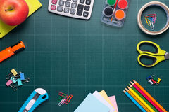 School and office supplies and apple in front of blackboard. Royalty Free Stock Images