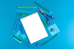 School office supplies on blue background stock photography