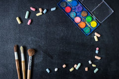 School and office supplies. Chalk scattered and paint brushes on the the old black board. Tools form the frame royalty free stock photos