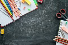 School and office supplies on a chalkboard background. Free space for text. Top view stock photo