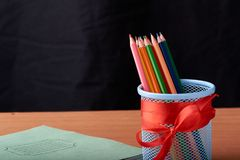 School and office supplies on classroom table in front of blackboard. View with copy space. School and office supplies on classroom table with big green pen in stock photography