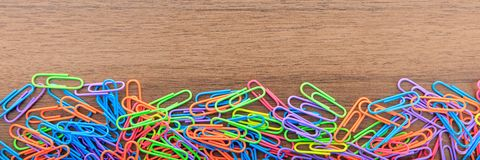 School, office supplies. Colorful paper clips on wood, banner. School, office supplies. Colorful paper clips on wooden background, banner, top view royalty free stock photos