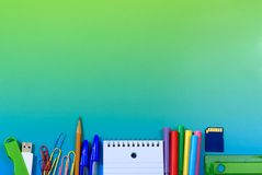 School or Office Supplies. School supplies create a lower border on a blue-green background. Supplies include a ruler, notepad, memory card, colored markers stock images