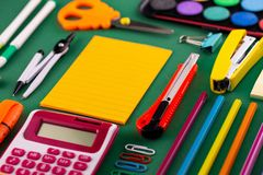 School office supplies stationery on a green background desk with copy space. Back to school concept.  stock image
