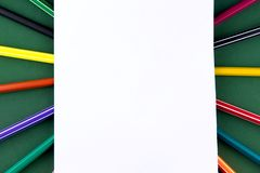 School office supplies stationery on a green background desk with white paper above copy space. Back to school concept.  royalty free stock photos