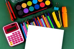 School office supplies stationery on a green background desk with white paper above copy space. Back to school concept.  royalty free stock photo