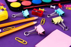 School office supplies stationery on a purple background desk. Back to school concept.  royalty free stock photography