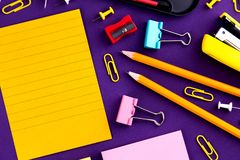 School office supplies stationery on a purple background desk with copy space. Back to school concept.  royalty free stock images