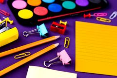 School office supplies stationery on a purple background desk with copy space. Back to school concept.  stock photo