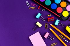School office supplies stationery on a purple background desk with copy space. Back to school concept.  royalty free stock image