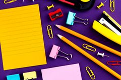 School office supplies stationery on a purple background desk with copy space. Back to school concept.  royalty free stock photos
