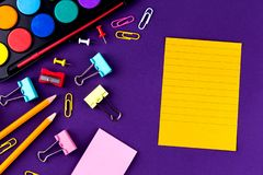 School office supplies stationery on a purple background desk with copy space. Back to school concept.  stock image