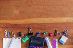 School or Office Supplies on Top of Wooden Table. Captured at Bottom Border Frame Royalty Free Stock Images