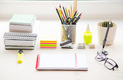School or office table near the window. Supplies and open notebook. stock photo