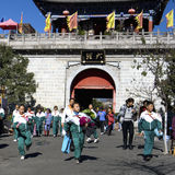 School is over. Schoolchildren in uniform going home on main street of Dali, Yunnan China with city  gate in background Stock Images