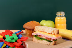 School packed lunch on classroom desk with blackboard, copy space Royalty Free Stock Photo