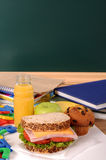 School packed lunch on classroom desk with blackboard, copy space, vertical Royalty Free Stock Photos