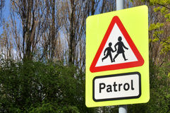School Patrol Crossing Sign. Typical school crossing patrol warning sign, with trees in the background Stock Image