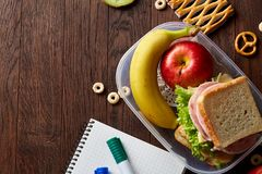 School or picnic lunch box with sandwich and various colorful vegetables and fruits on wooden background, close up. Royalty Free Stock Photos