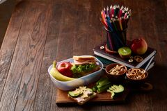 School or picnic lunch box with sandwich and various colorful vegetables and fruits on wooden background, close up. Royalty Free Stock Photo