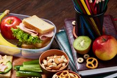 School or picnic lunch box with sandwich and various colorful vegetables and fruits on wooden background, close up. Stock Photo