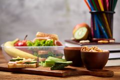 School or picnic lunch box with sandwich and various colorful vegetables and fruits on wooden background, close up. Stock Image