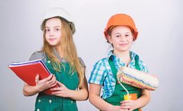 School project. small girls repairing together in workshop. Labor day. 1 may. Little kids in helmet with tablet and royalty free stock image
