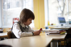 School pupil sits at school with cell phone Stock Photo