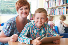 School Pupil With Teacher Using Digital Tablet In Classroom Stock Photo