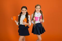 School routine. Having break relax. Drinking tea while break. School mates relaxing with drink. Enjoy being pupil. Girls. Kids school uniform orange background stock image