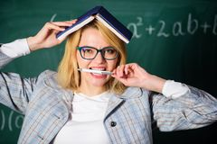 School daily routine. Teacher stress and burnout. Overwork and lack of support driving teacher out of profession. Teacher woman with book chalkboard background royalty free stock image