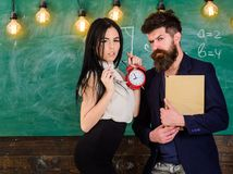 School rules concept. Lady teacher and strict schoolmaster care about discipline and rules in school. Man with beard. Hold book and girl teacher holds alarm stock photography