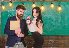 School rules concept. Man with beard hold book and girl teacher holds alarm clock, chalkboard on background. Lady. Teacher and strict schoolmaster care about royalty free stock photography