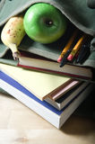 School Satchel with Books and Fruit. An open school satchel, containing books, pens, pencils and fruit.  Vertical (portrait) orientation Stock Images